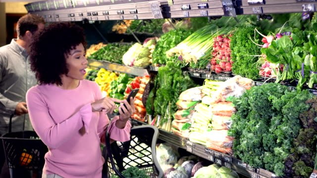 young woman buying groceries, shopping list on phone - kale stock videos and b-roll footage