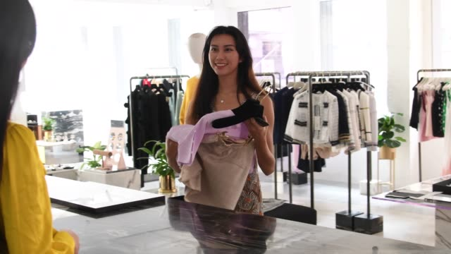 young woman buying new clothes in boutique - 20 24 years stock videos & royalty-free footage