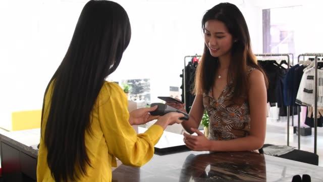 vidéos et rushes de jeune femme acheter de nouveaux vêtements à l'aide de smartphone sans contact - sac de shopping