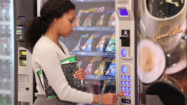 ms td young woman buying snack from vending machine in cafeteria / richmond, virginia, usa - snack stock videos & royalty-free footage