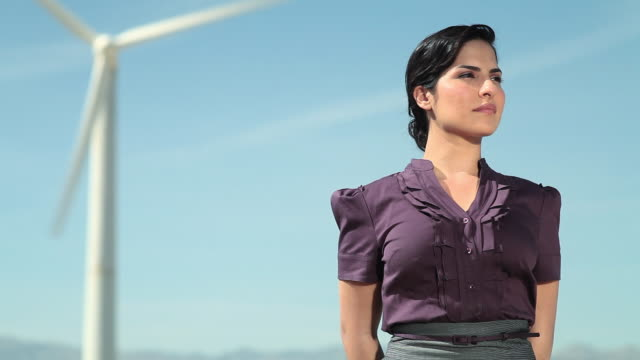 young woman by a wind turbine - bluse stock-videos und b-roll-filmmaterial