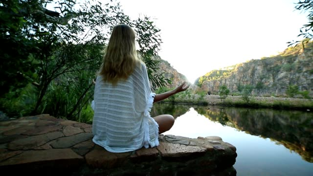 young woman by the lake exercises yoga in lotus position - zen like stock videos & royalty-free footage
