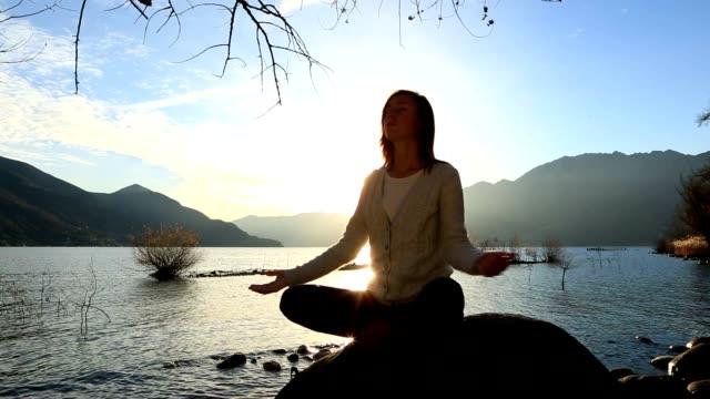 ung kvinna vid sjön utövar yoga i solnedgången - utsträckta armar bildbanksvideor och videomaterial från bakom kulisserna