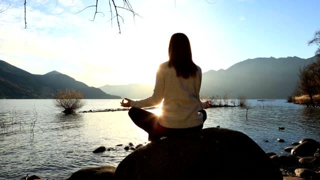 junge frau am see ausübung yoga bei sonnenuntergang - zen stock-videos und b-roll-filmmaterial