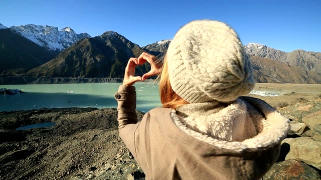 Young woman by the lake makes a heart shape finger frame