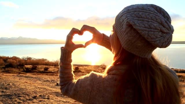 Junge Frau am See macht ein Formrahmen Finger Herz