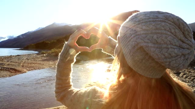 Young woman by the lake makes heart shape finger frame