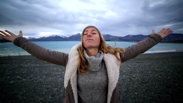 vídeos de stock, filmes e b-roll de jovem mulher pelos braços estendidos lakeshore - mãos estendidas