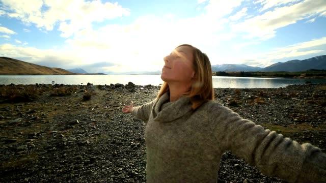 vídeos de stock e filmes b-roll de young woman by the lakeshore arms outstretched - gorro de lã