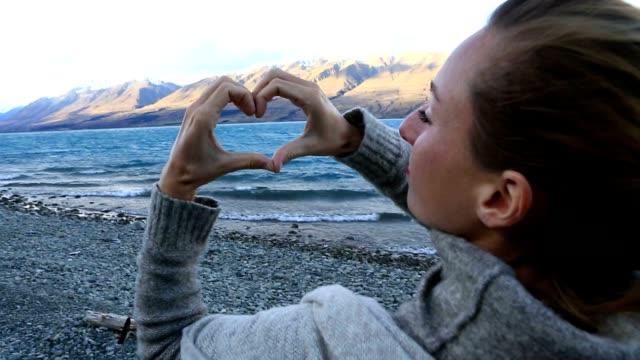 vídeos de stock, filmes e b-roll de jovem mulher pela margem da lago faz um frame de dedo de forma de coração na paisagem do lago de montanha - símbolo conceitual