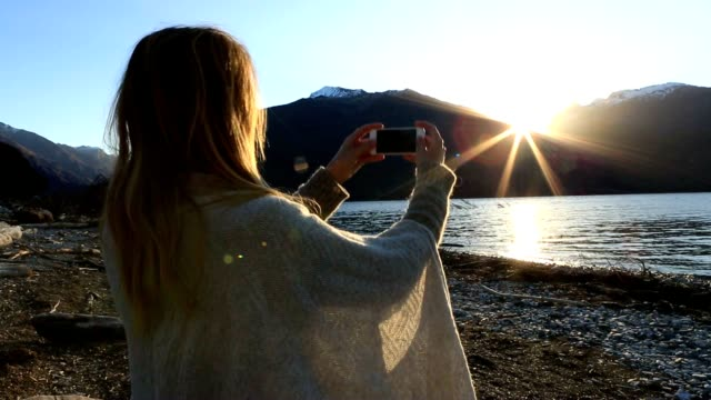 young woman by the lakeshore taking a picture of the beautiful sunset using a smart phone - lakeshore stock videos & royalty-free footage