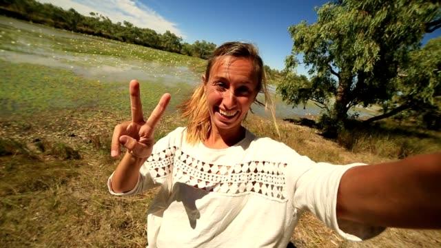 Jonge vrouw door de rivier neemt een selfie-portret