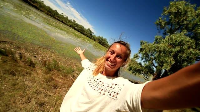 vídeos y material grabado en eventos de stock de joven por el río toma un retrato selfie - posa del loto