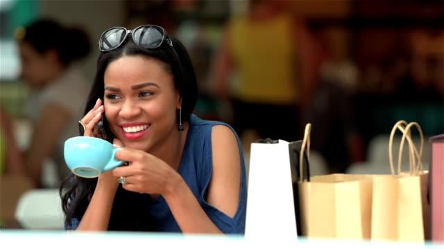 Jonge vrouw belt een vriend terwijl het hebben van een kopje koffie