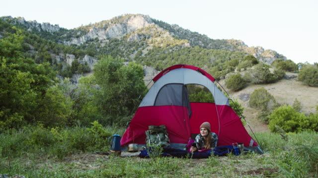 young woman camping in the mountains - endast unga kvinnor bildbanksvideor och videomaterial från bakom kulisserna