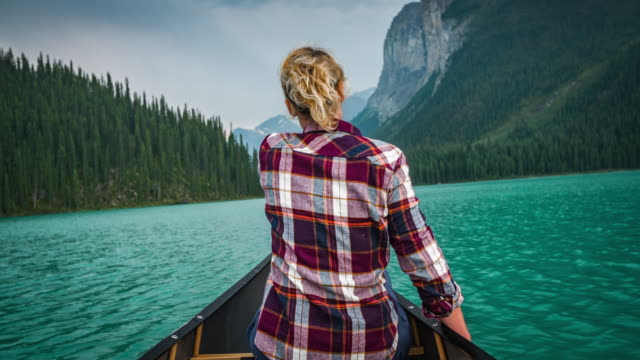 young woman canoeing on maligne lake - pagaiare video stock e b–roll