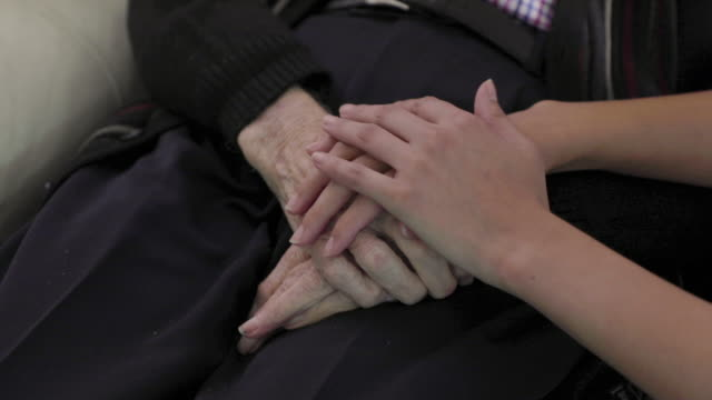 a young woman cares for an old man - the ageing process stock videos & royalty-free footage