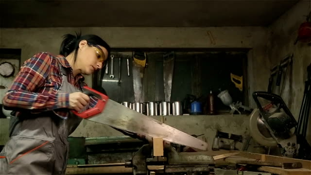 Young woman carpenter cutting a board whit saw