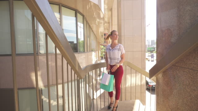 Young woman carries shopping bags, in city center