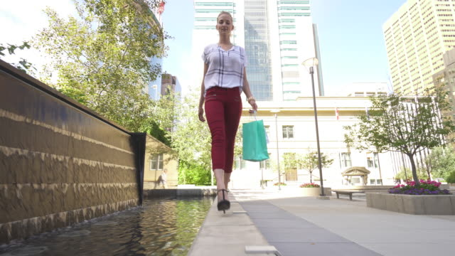 young woman carries shopping bags, in city center - high heels stock videos & royalty-free footage