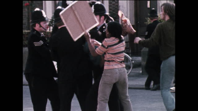 young woman carrying a sign saying 'pig' tries to stop police arresting a fellow protestor during a demonstration against the repeated police raids... - young women stock videos & royalty-free footage