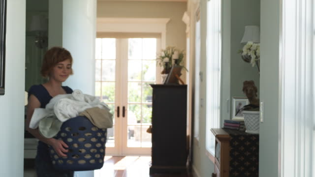stockvideo's en b-roll-footage met ms young woman carrying laundry basket through hallway, phoenix, arizona, usa - de was doen