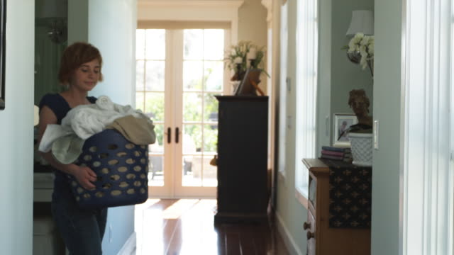stockvideo's en b-roll-footage met ms young woman carrying laundry basket through hallway, phoenix, arizona, usa - mand