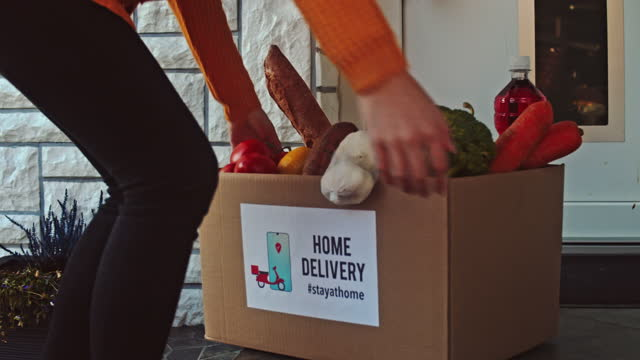 slow motion young woman carrying the food box to the doorstep - shopping bag stock videos & royalty-free footage