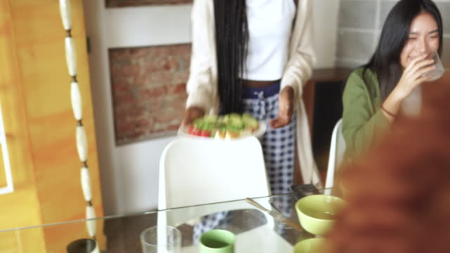 Young woman carrying vegan breakfast to the kitchen table