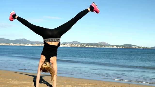 young woman cartwheeling at beach - upside down stock videos & royalty-free footage