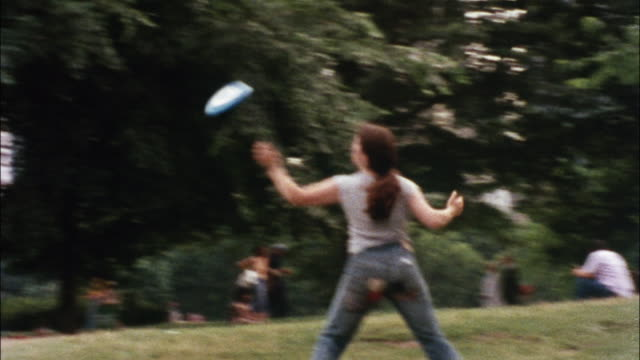 vidéos et rushes de a young woman catches a frisbee and spins it on her finger in new york city's central park. - central park manhattan