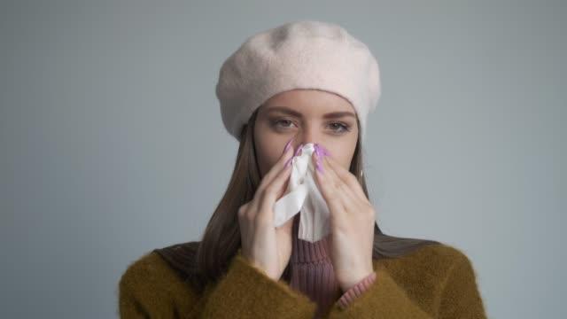 vidéos et rushes de jeune femme attrapant un rhume - attraper