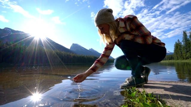 Jonge vrouw vangen van vers water uit bergmeer, Canada