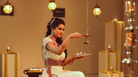 young woman celebrating diwali festival with her daughter - focus on background stock videos & royalty-free footage