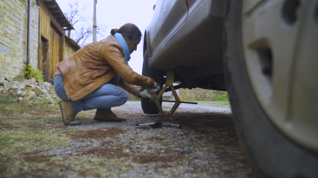 young woman changing car tire on a country road. diy - tyre stock videos & royalty-free footage