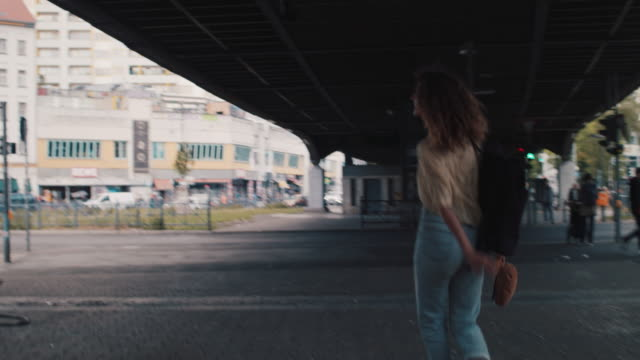 young woman chasing pigeons under bridge in berlin, germany - chasing stock videos & royalty-free footage
