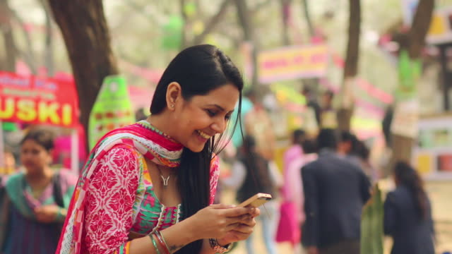 young woman chatting on a mobile phone, suraj kund fair, faridabad, haryana, india - indien stock-videos und b-roll-filmmaterial