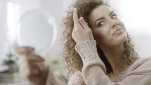 young woman checking her hair in mirror - adjusting stock videos & royalty-free footage