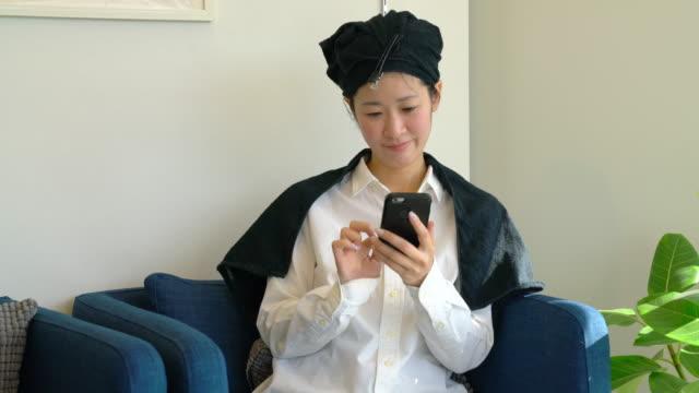 若い女性の髪の乾燥を待っている間に美容室で彼女の携帯電話をチェック