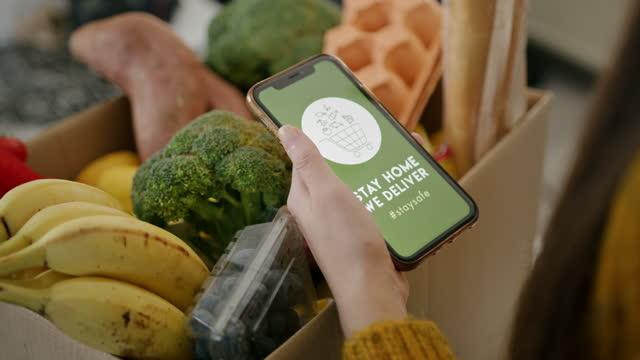 vidéos et rushes de slow motion jeune femme vérifiant l'application de livraison à domicile devant la boîte de nourriture - produit bio