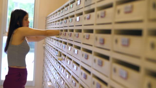 vidéos et rushes de jeune femme vérifie les mails - poteau en bois