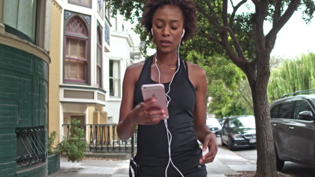 young woman checking mobile phone app after running outdoors in san francisco - wellbeing stock videos & royalty-free footage