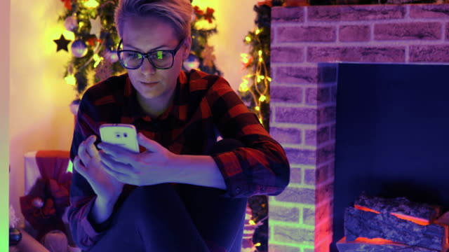young woman checking out her text messages on her mobile phone as she sits cross-legged on the floor in front of the christmas tree at home. - woman cross legged stock videos & royalty-free footage