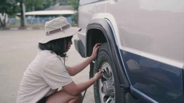 若い女性チェック タイヤ空気圧とタイヤに空気を充填します。 - touching点の映像素材/bロール