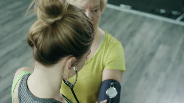 A young woman checks blood pressure In The Gym