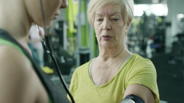 a young woman checks blood pressure in the gym - measuring stock videos & royalty-free footage