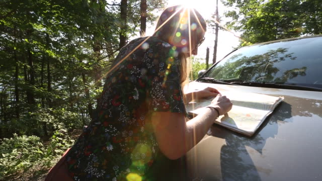 young woman checks map on hood of car - only mid adult women stock videos & royalty-free footage