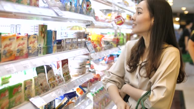 Young woman chooses dairy produce in the store
