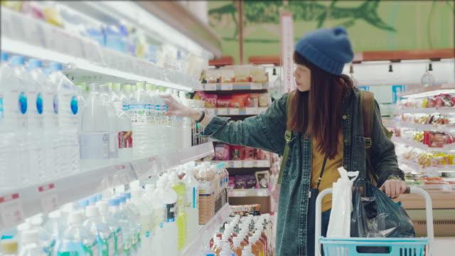 若い女性により乳製品を保存する - 小売り点の映像素材/bロール