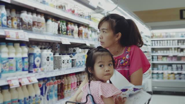 stockvideo's en b-roll-footage met jonge vrouw kiest zuivelproducten met haar baby meisje in de winkel - dairy product